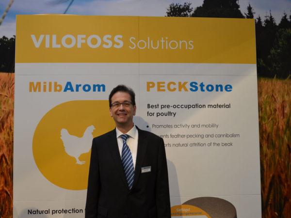 Dr. Egbert Strobel, Fachberater im Bereich Geflügel, vor einem Plakat der VILOFOSS Solutions Gruppe.